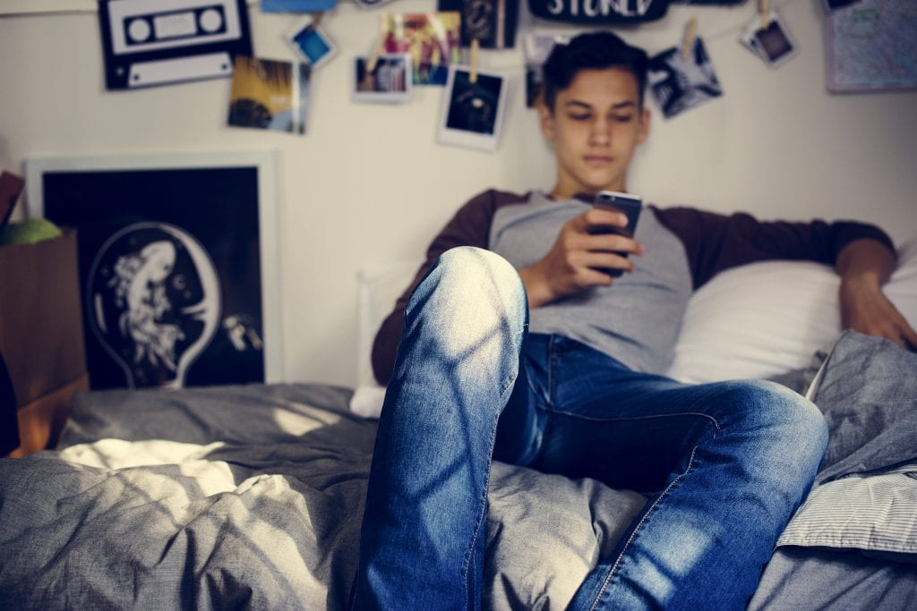 Male teen sitting in room on his phone