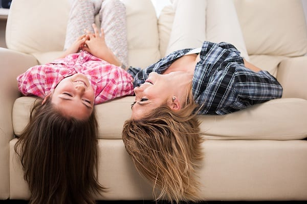 Two teen girls laying on sofa smiling